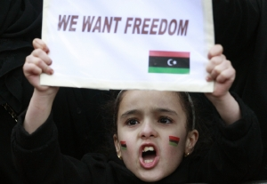 A child joins demonstrators protesting against Libya's Muammar Gaddafi outside the Libyan Embassy in London